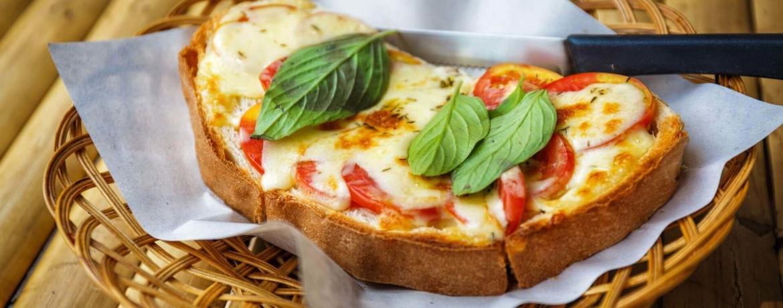 Überbackenes Brot mit Käse, Tomaten und Basilikum