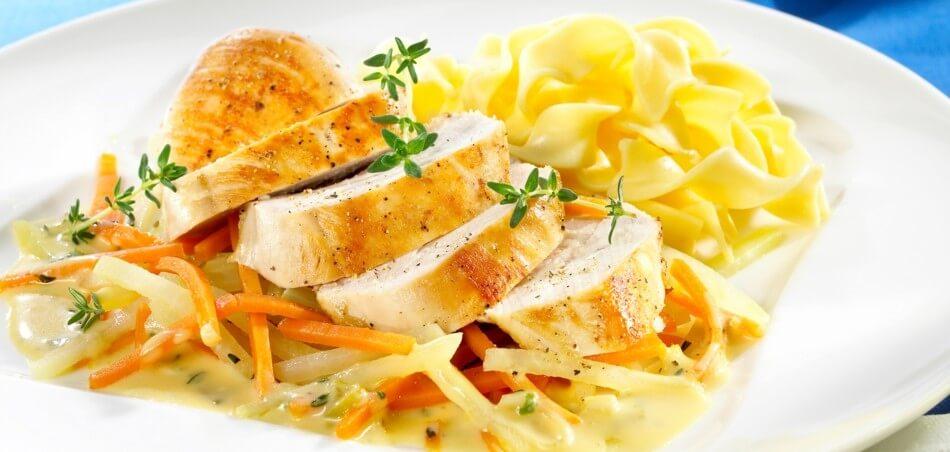 Gebratenes Thymian-Hähnchen an Gemüse von Kohlrabi und Karotte auf Tagliatelle