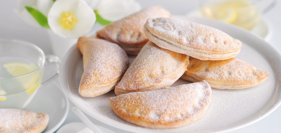 Russische Piroggen - gebackene Piroschki-Teigtaschen mit Füllung aus Apfel
