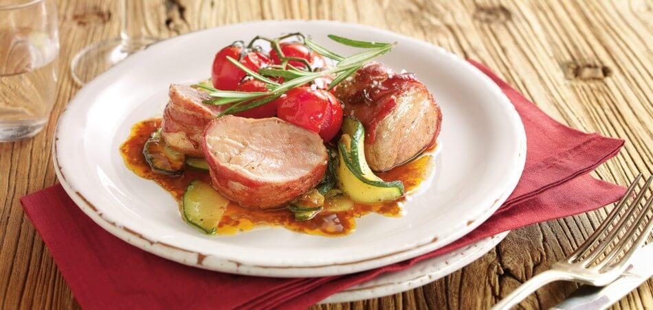 Schweinemedaillons im Speckmantel mit gerösteten Tomaten und Gemüse von der Zucchini