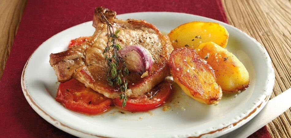 Koteletts vom Schwein an gebratenen Tomaten und mit Knoblauch und Thymian verfeinerter Kräuterbutter