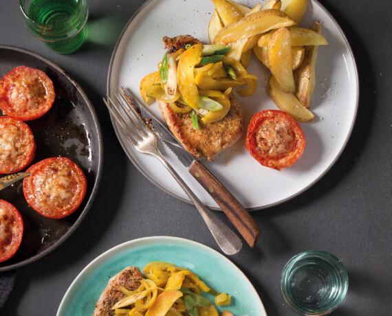 Schweine-Steak mit Apfel-Curry-Zwiebeln, Ofenkartoffeln und würzig gegrillter Tomate